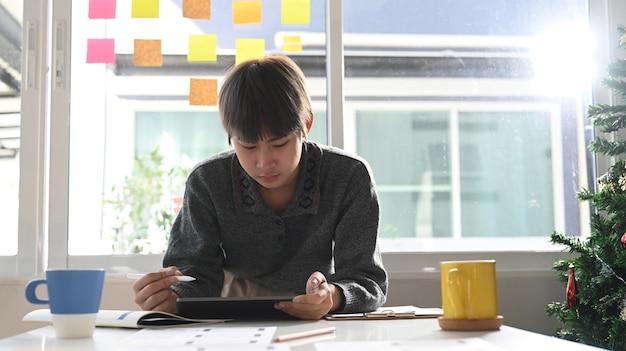 彼女のワークステーションに立っている間デジタルタブレットで描く若い女性のクリエイティブデザイナーまたはグラフィックデザイナー。