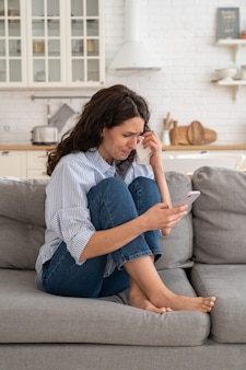 若い女性が泣いて悪いニュースを読む