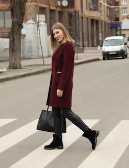 街の通りを渡る若い女性