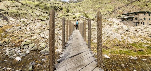 木製の橋を渡り、山でハイキングする若い女性。スペイン、カスティーリャイレオンのアビラ、グレドスサーカスの大きなラグーン。