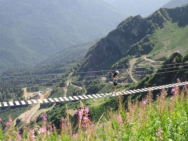 Young woman crossing the chasm on the rope bridge, sochi, russia