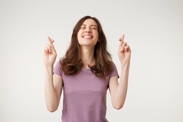 Молодая женщина, скрестив пальцы и желая удачи
