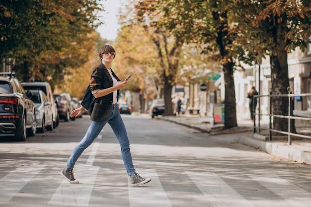 道路を横断し、電話を使用して若い女性