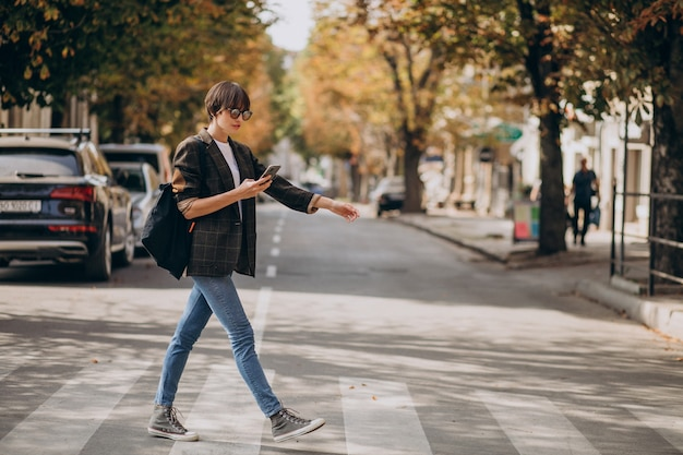 Young woman crossing road and using phone