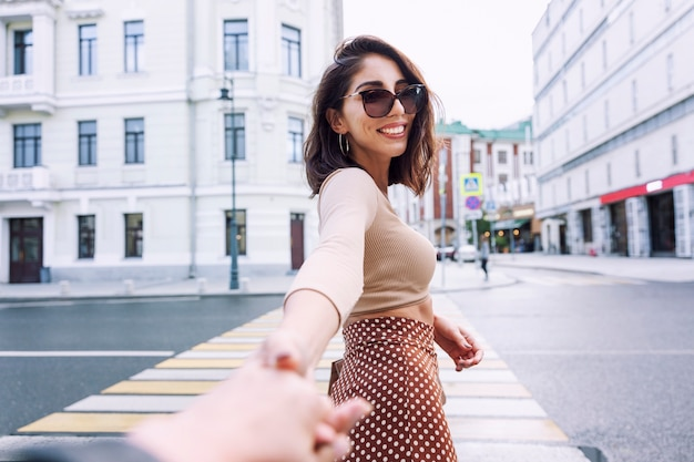 Young woman at a crosswalk in the city. smiling brunette holds her hand.