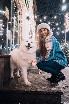 冬の通りに犬の横にうずくまって若い女性