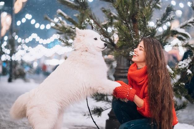 Молодая женщина присела рядом с собакой на зимней улице