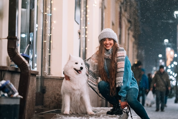 Young woman crouched beside a dog on a winter street