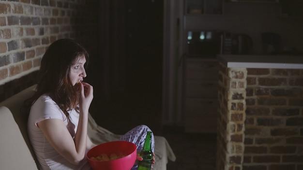 Tv 앞에서 울고 와인을 마시는 젊은 여자.