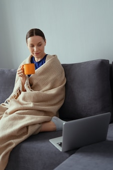 Young woman cuddling in a warm blanket with a laptop and cup of tea
