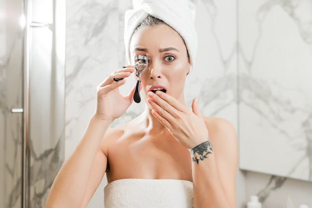 Young woman curling eyelashes with a curler wrapped in towels in the bathroom