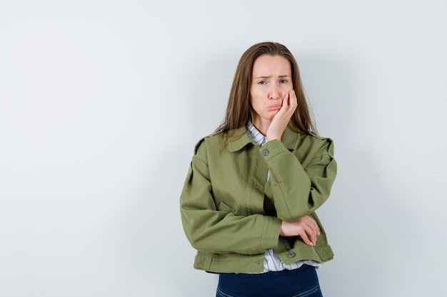 若い女性は唇を曲げ、シャツ、ジャケットのポーズを考えて立って、落ち込んでいます。正面図。