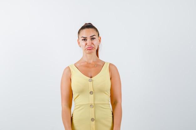 Giovane donna che curva il labbro inferiore in vestito giallo e sembra all'oscuro. vista frontale.