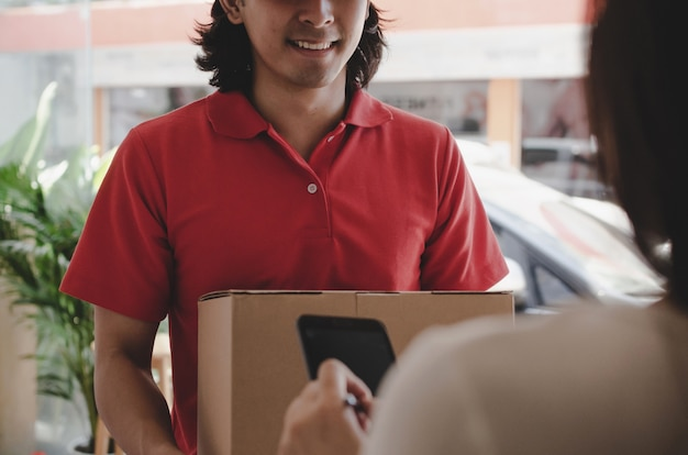 Young woman customer appending signature in digital mobile phone receiving parcel post box from courier