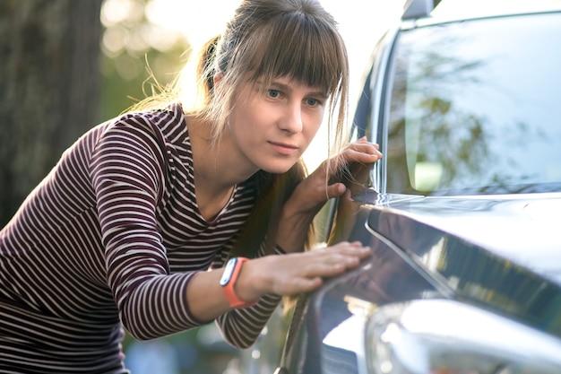 젊은 여성 고객이 새 차를 구입하기 전에 딜러 야외 상점에서 새 차를 자세히 살펴봅니다.