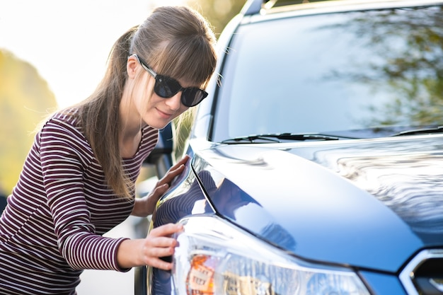 Young woman customer closely examining a new car at dealer outdoor shop before purchasing it.