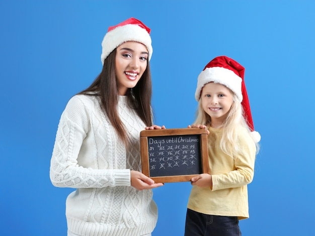 Young woman and cute little girl in santa hats with chalkboard counting days until christmas, on color background