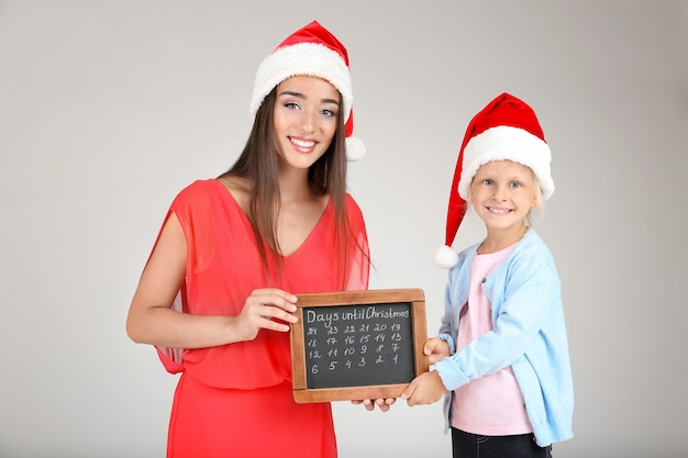 Young woman and cute little girl in santa hats with chalkboard counting days until christmas, on light background