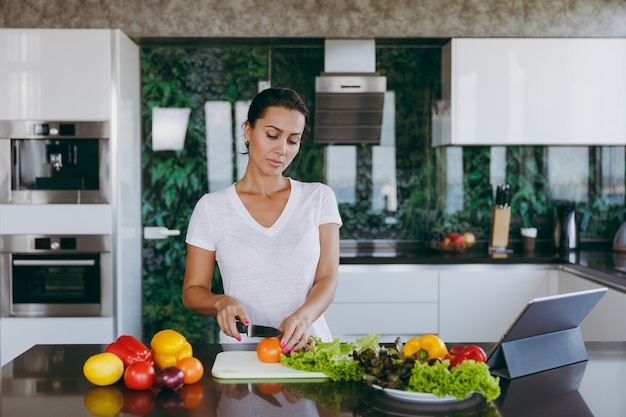The young woman cuts vegetables in the kitchen with a knife and laptop on the table