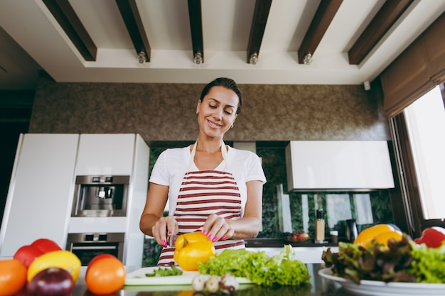The young woman cuts vegetables in the kitchen with a knife