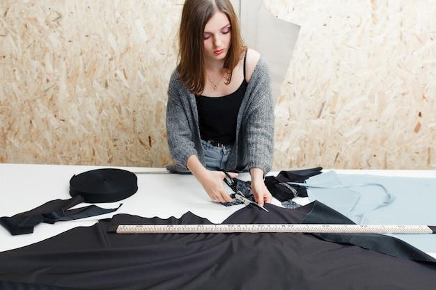 ワークショップで黒い布を切る若い女性。