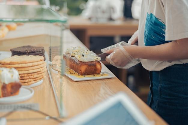 ベーカリーショップでケーキを切る若い女性
