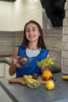 Kitche 나무 테이블에 건강 식품을 요리하는 다른 과일을 절단하는 젊은 여자. 요리 준비