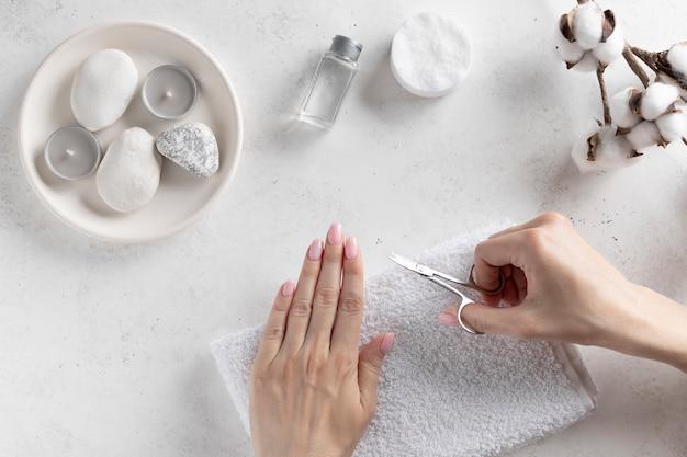 Молодая женщина резки ногтей с маникюрными ножницами. концепция гигиены. белая стена со свечами и цветок хлопка. вид сверху. копировать пространство