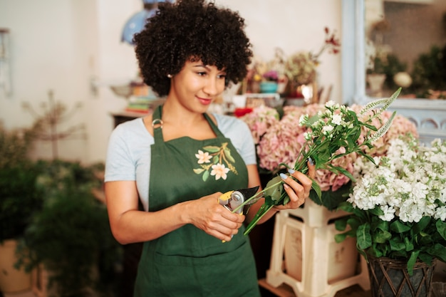 Young woman cutting stem of flowers with secateurs in flower shop