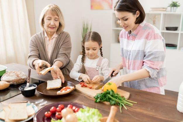 Молодая женщина режет помидоры на борту, а ее дочь и мать делают бутерброды на кухне