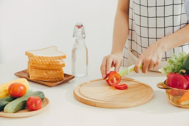 台所で野菜を切る若い女性