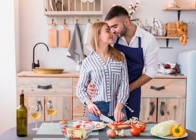 Young woman cutting vegetables while man hugging her