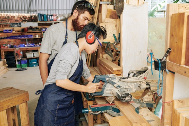 Young woman cutting wood plank with circular saw under control of her coworker