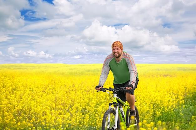 노란 꽃밭에서 자전거를 타는 젊은 여성