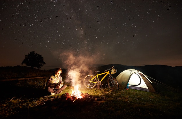Young woman cyclist having a rest at night camping near burning campfire, illuminated tourist tent, mountain bike under beautiful evening sky full of stars