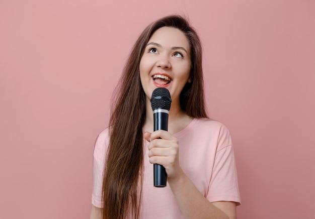 Молодая женщина балуется, прищуривает глаза с микрофоном в руке на розовом фоне