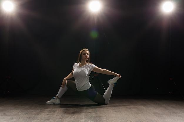 젊은 여성 댄서 체조 운동은 어두운 배경에서 포즈를 취합니다.