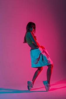 밝은 분홍색 자외선으로 스튜디오에서 포즈를 취하는 운동화를 신고 세련된 후드티를 입은 젊은 여성 댄서. 디스코 스타일의 네온 다색 색상으로 춤을 추는 현대적인 세련된 소녀.