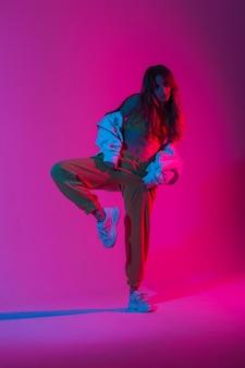 밝은 분홍색 자외선이 있는 방에서 한쪽 다리에 포즈를 취한 운동화를 신고 세련된 상의를 입은 젊은 여성 댄서. 네온 다색 색상으로 실내에서 춤을 추는 멋지고 현대적인 세련된 소녀.