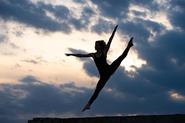 야외 일출에 점프하는 젊은 여자 댄서