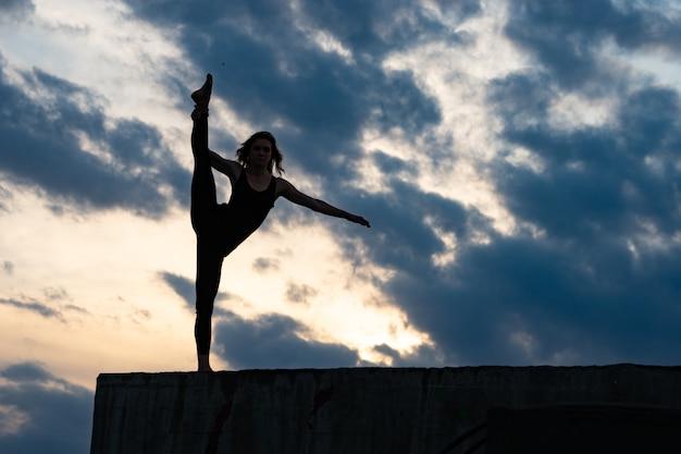 야외 일출에 젊은 여자 댄서입니다.