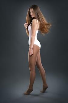 暗い背景の若い女性ダンサー