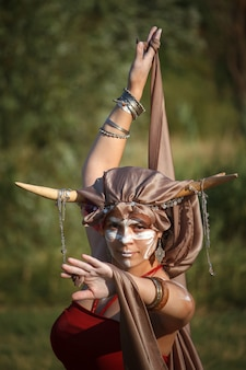 Young woman dancer with painted face and horns on her head is standing in the dance pose and looking at the camera