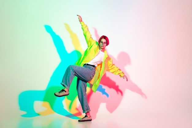 네온으로 스튜디오 배경에서 격리된 힙합, 스트리트 스타일을 춤추는 젊은 여성. 패션과 모션, 청소년, 음악, 액션 컨셉. 광고에 대 한 copyspace입니다.