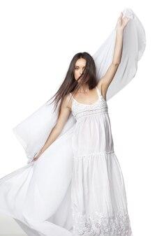 흰색 위에 화려한 흰색 드레스를 입고 춤을 추는 젊은 여자