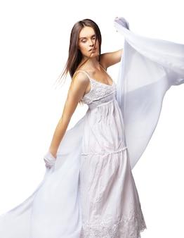 화려한 흰색 드레스를 입고 춤을 추는 젊은 여자