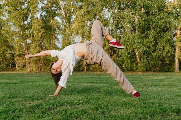 Молодая женщина танцует на открытом воздухе на зеленой траве