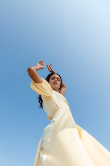 Young woman dancing on sky background
