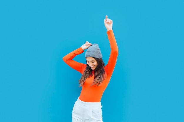 Young woman dancing with arm raised in front of blue backdrop