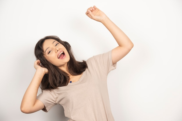 Young woman dancing with hands up on white background.